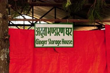 Affiche en népalaisdevant un long drap rouge qui montre où est entreposé le gingembre bio