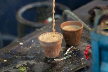 Chaï en train d'être versé dans un verre de terre cuite par un vendeur de chaï en Inde (chai wallah)