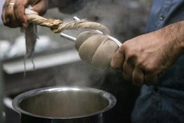 Vendeur de chaï, en Inde, en train de serrer un linge avec des épices au dessus d'une gamelle