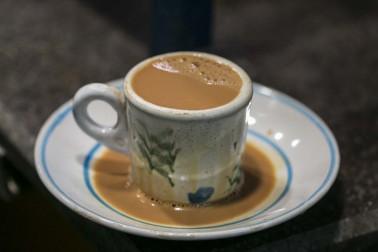 Tasse à thé sur une soucoupe et remplie de chaï qui a débordé dans la soucoupe