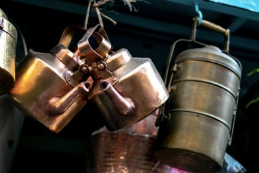 Théières et lunch box accrochées sur le stand d'un vendeur de chaï
