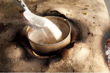 Marmite enfouie en terre, sur un feu, remplie de chaï