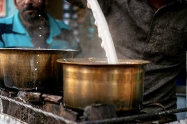 Vendeur de chaï en Inde en train de verser du lait dans une marmite