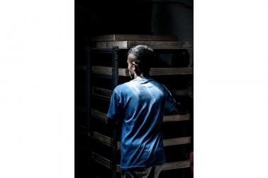 Personne de dos poussant un chariot rempli de noix de muscade, dans l'entrepôt des producteurs d'épices