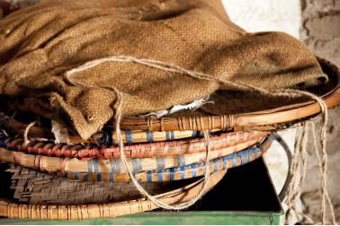 Pile de volets servant à trier les épices et couverts par une toile de jute, au Népal