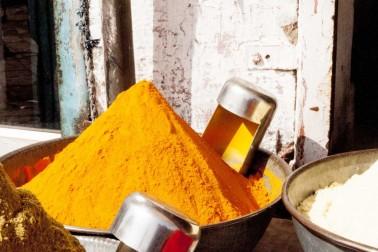 Curcuma en poudre dans un grand plateau au marché en Inde