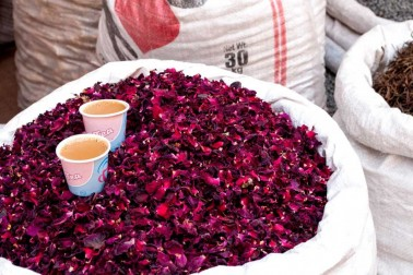 2 verres de chaï masala posés sur un sac de pétales de rose