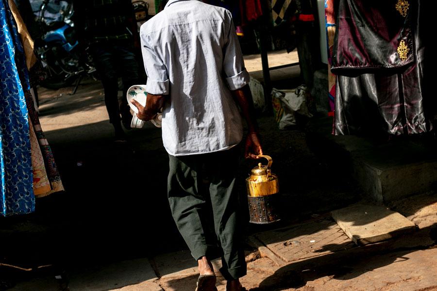 Vendeur de chaï de dos qui marche dans la rue, une grosse théière à la main