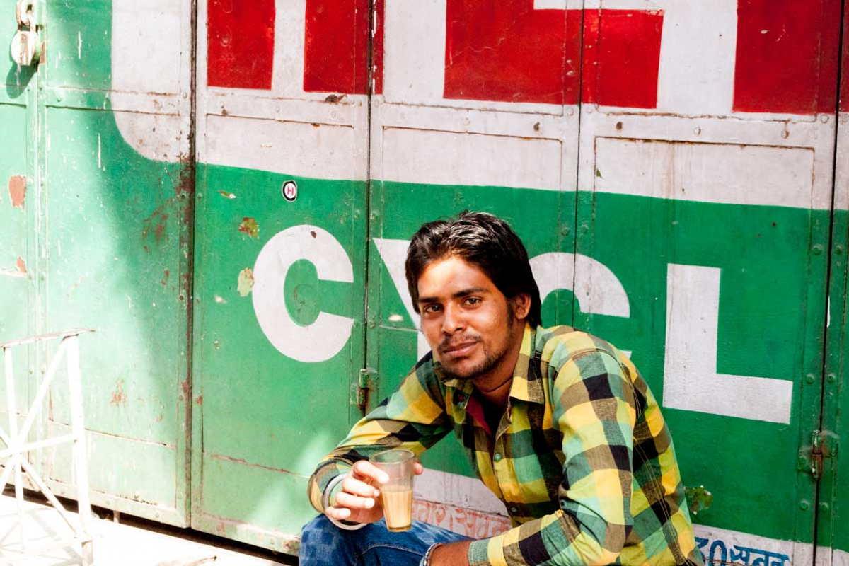 Jeune indien assis buvant un verre de chaï