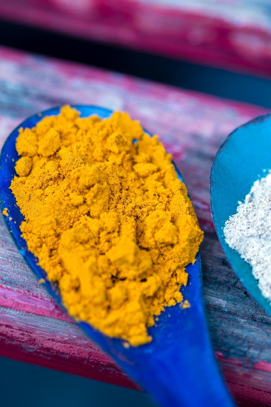 Curcuma en poudre très orange dans une cuillère bleue